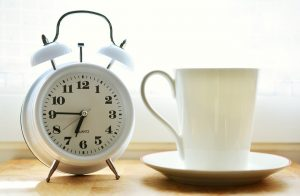 A white alarm clock next to a coffee cup.