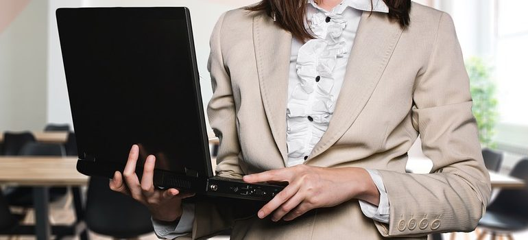 a woman holding a laptop and getting ready to focus on website management