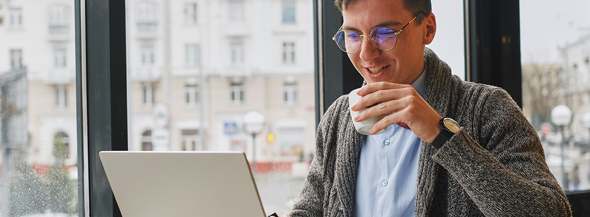 Man looking at laptop while drinking a coffee