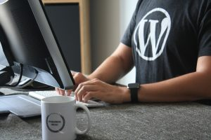 a guy in a wordpress logo t-shirt sitting in front of a computer
