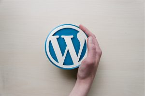 A hand holding a WordPress sign.