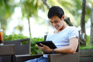 A man holding a tablet, reading about hosting videos on WordPress.