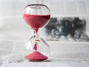 An hourglass with pink sand.