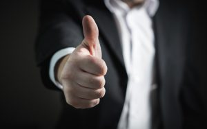 A man in a suit giving a thumbs-up gesture.
