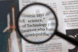 A magnifying glass held over a piece of text.