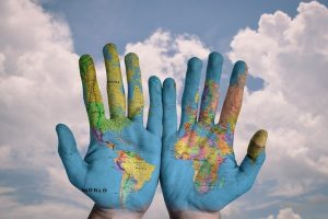 Hands painted in blue, showing a map of the world.