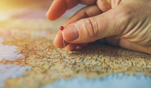 A man holding a red pin in front of a map.