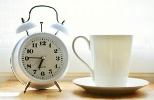 A white alarm clock next to a white mug.