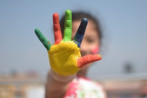 A girl with painted fingers.