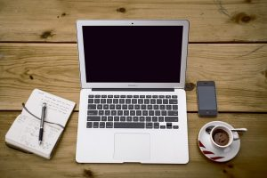 A notebook, a cup of coffee, and a phone next to a laptop.