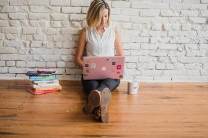 A girl holding a laptop in her lap, learning what is UX.