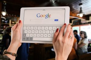 A woman looking at Google on a white tablet