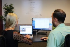 Two people on laptops, trying to display related posts in WordPress.