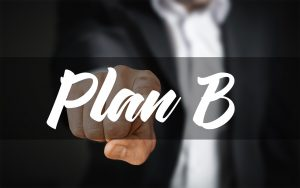 A man pointing at plan B on the screen.