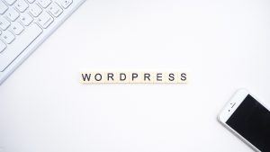 Letter tiles spelling out 'wordpress', a white computer keyboard, and a white mobile phone