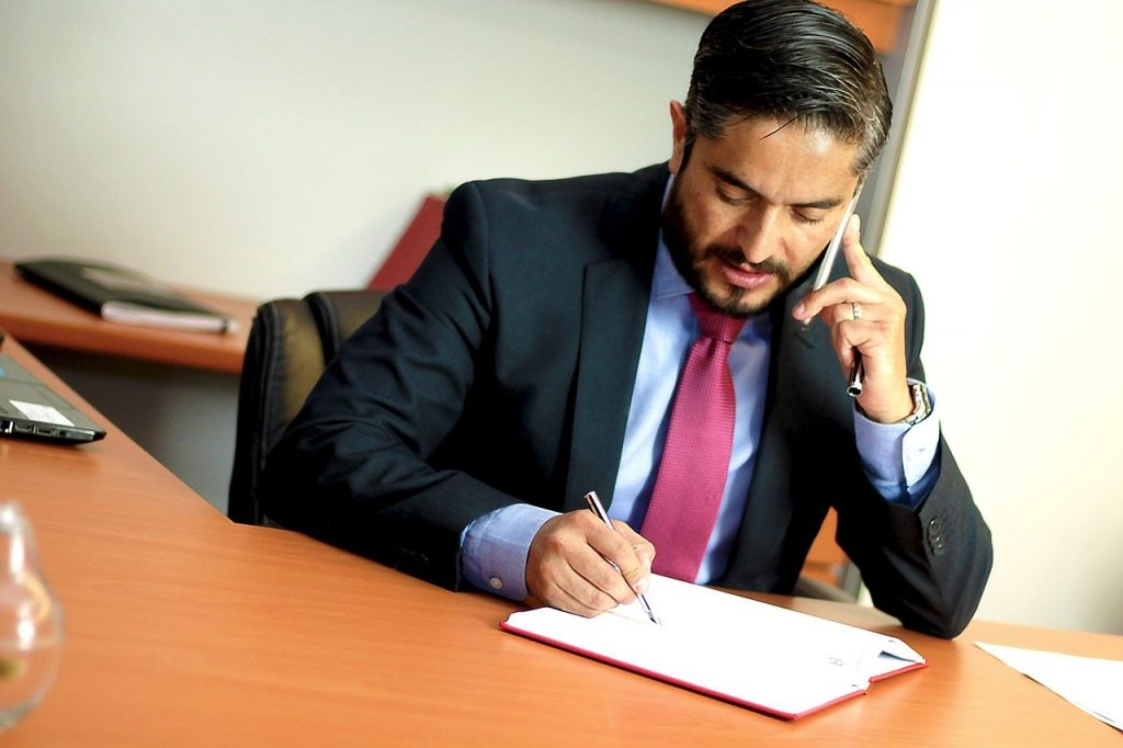A man on the phone while looking at a contract.