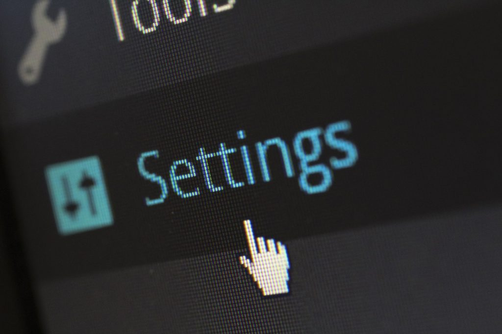 A mouse pointer hoovering over Settings button in WordPress.