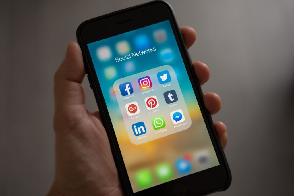 A hand holding a phone displaying the open folder containing nine different social media icons