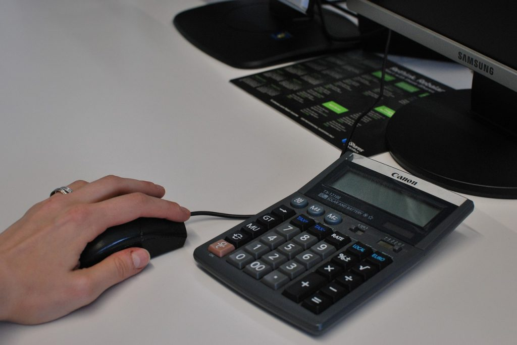 A person holding a mouse while working on a computer, representing the need to track link clicks and button clicks in WordPress.
