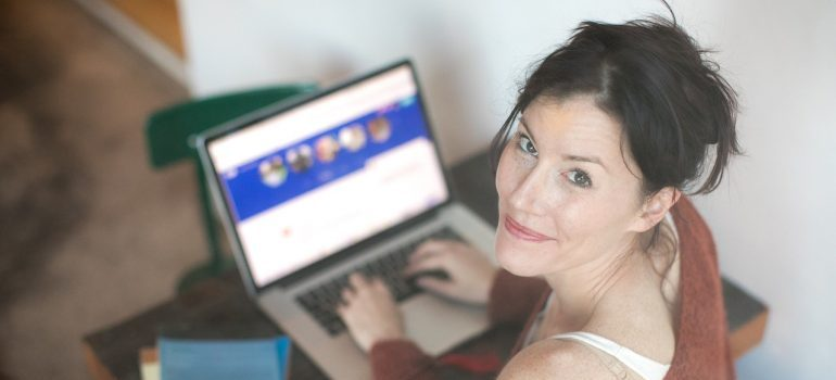 A woman browsing websites with WordPress footer on a laptop.
