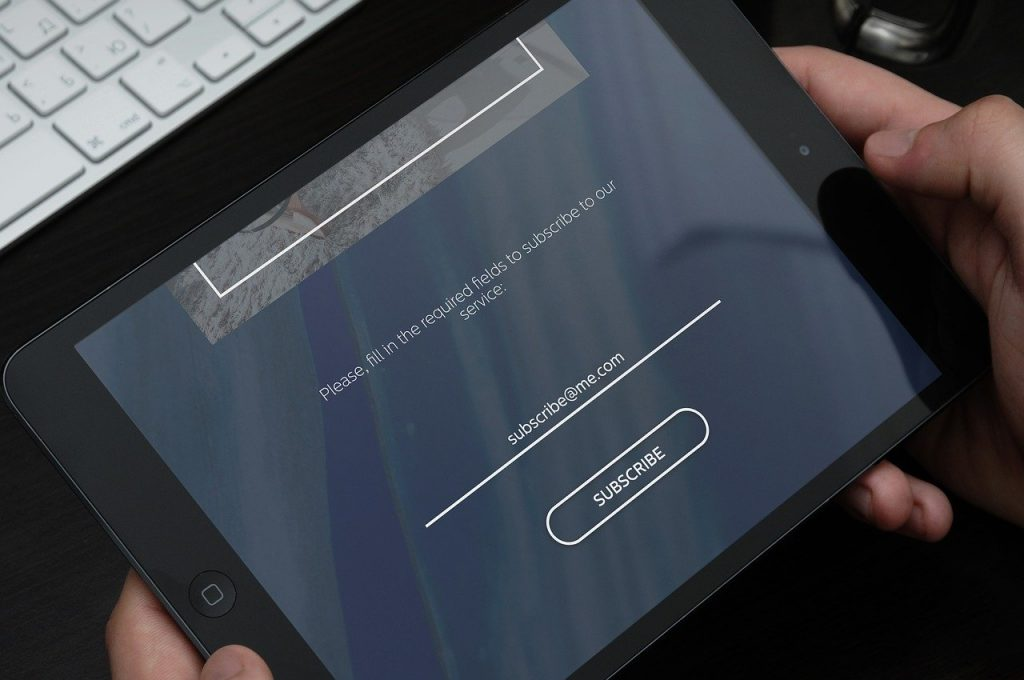 A person holding a tablet in order to subscribe to a website.