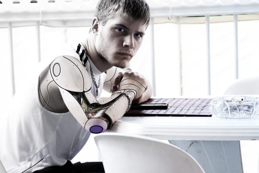 An robot with a human face sitting at a computer representing the core reason why you need to add reCAPTCHA to WordPress comment form.