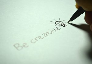 """Writing """"be creative"""" with a light bulb on the paper."""