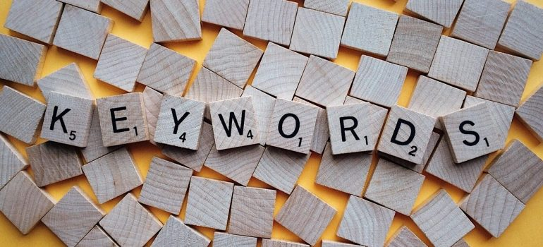 Keywords written in Scrabble blocks, showing you that using them is one of the easiest SEO tricks for creating SEO friendly URLs.