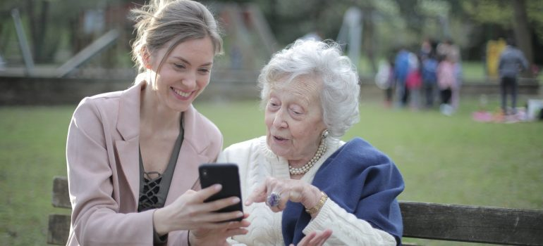 A girl showing something on a phone to her grandmother.