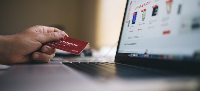 A person holding a credit card while looking at an online store.