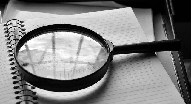 A magnifying glass on a notebook.