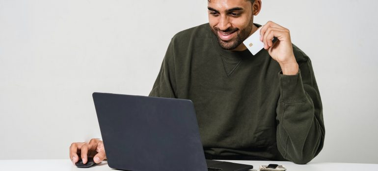A person smiling while looking at a website on their laptop.