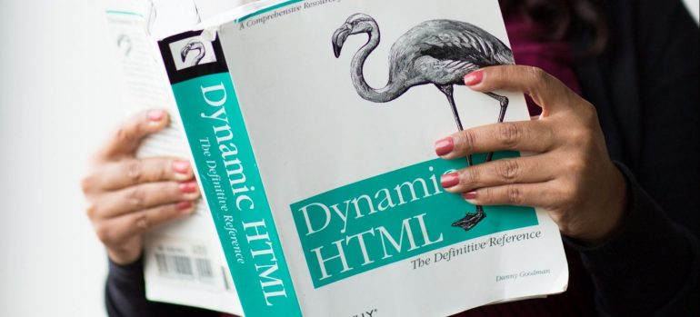 A person reading a book on Dynamic HTML before they move a website to a new host.