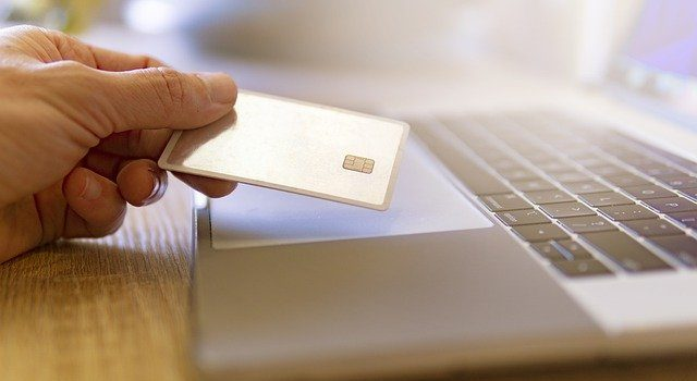 Holding a credit card when making online payments.