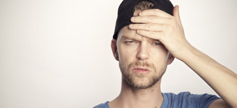 A person holding their forehead after trying to add image hover effects in WordPress without making a backup.