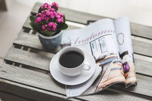 Reading an engaging magazine while enjoying a coffee.