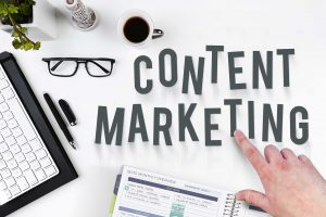 """Pointing at the """"Content Marketing"""" words on a table with a keyboard and notebook full of writings."""