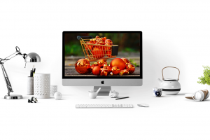 Several purchased online products around the monitor with a full shopping cart in the picture.
