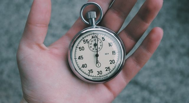 A hand holding an old stopwatch.