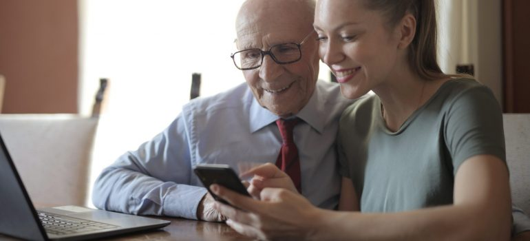 A girl navigating a website along with her grandfather.