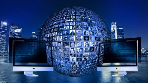 A globe of numerous online visitors' pictures between two computer monitors.