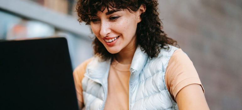 Smiling woman at a laptop.